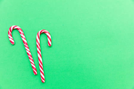 Christmas time. Candy canes on green background, copy space