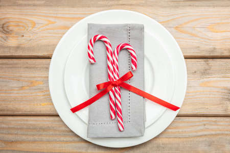 Christmas table setting. Candy canes and a grey napkin on white plates, wooden background, top view