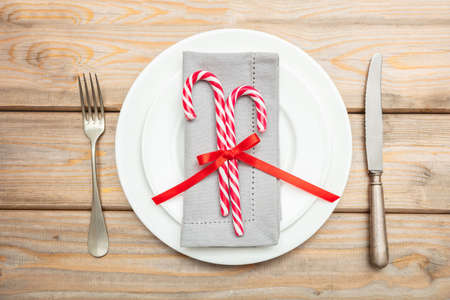 Christmas table setting. Candy canes on white plates and cutlery, wooden background, top view