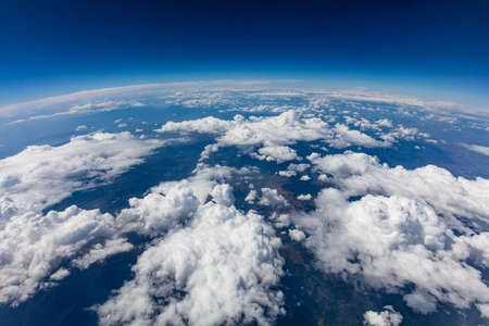 Curvature of planet earth. Aerial shot. Blue sky and clouds over land