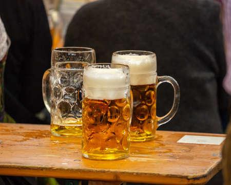 Mugs of Bavarian beer on a wooden desk, closeup view. Oktoberfest, Munich, Germany.