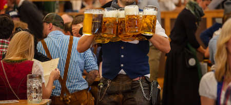 Oktoberfest, Munich, Germany. Waiter with traditional costume serving beers, closeup view