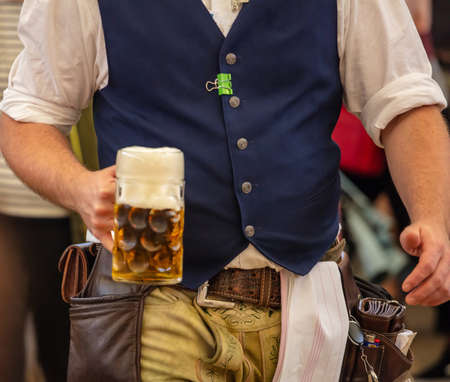 Oktoberfest, Munich, Germany. Waiter with traditional costume holding one beer, closeup view
