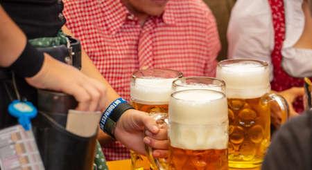 Oktoberfest, Munich, Germany. Woman waiter serving beers, closeup view Stock fotó