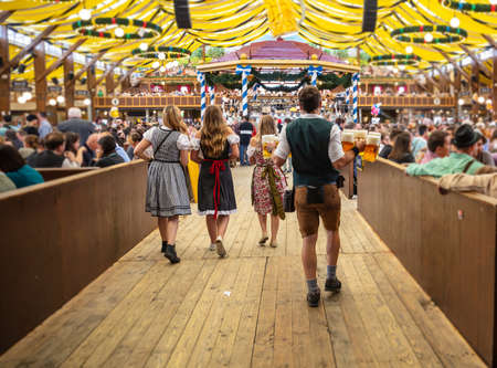 Oktoberfest, Munich, Germany. Waiter with traditional costume holding beers, crowded tent interior background Stock fotó