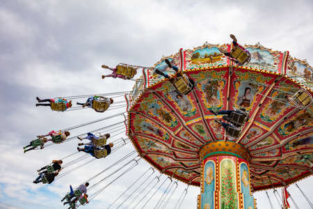 Colorful carousel on cloudy sky background. Oktoberfest, Bavaria, Germany