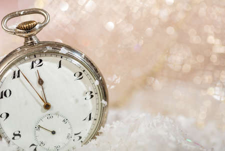 New Years eve party celebration. Minutes to midnight on an old watch, bokeh snowy background, copy space Banco de Imagens