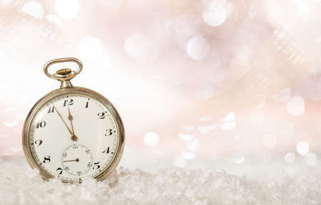 New Years eve countdown. Minutes to midnight on an old fashioned pocket watch, bokeh snowy background, copy space