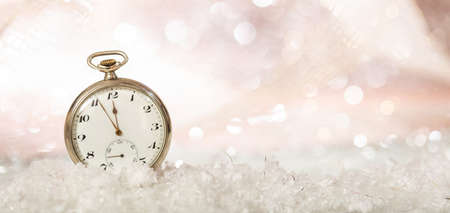 New Years eve party celebration. Minutes to midnight on an old fashioned pocket watch, bokeh snowy background, copy space, banner,