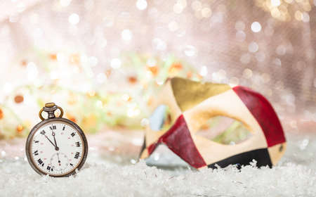 Carnival party countdown. Minutes to midnight on an old watch, colorful mask, bokeh festive background