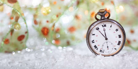 New Years eve countdown. Minutes to midnight on an old watch, bokeh background, copy space