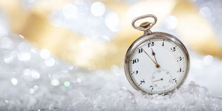 New Years eve countdown. Minutes to midnight on an old pocket watch, bokeh background, copy space Stock Photo
