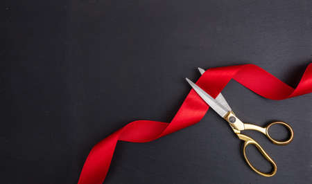 Grand opening. Top view of gold scissors cutting red silk ribbon against black background, copy space Foto de archivo
