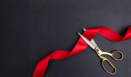 Große Eröffnung. Blick von oben auf die Goldschere, die rotes Seidenband auf schwarzem Hintergrund schneidet, Kopierraum