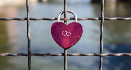 Lock your love for ever. Pink heart shaped padlock on a link fence against blurry river background.