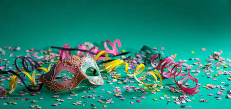 Carnival party. Colorful mask, streamers and confetti on bright green background, banner 免版税图像