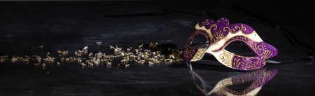 Carnaval tijd. Venetiaans masker paarse en gouden kleur op zwarte achtergrond, reflecties, banner Stockfoto
