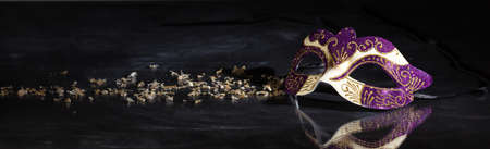 Carnival time. Venetian mask purple and gold color on black background, reflections, banner