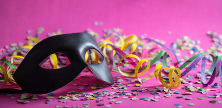Carnival party. Black mask, streamers and confetti on bright pink background, banner