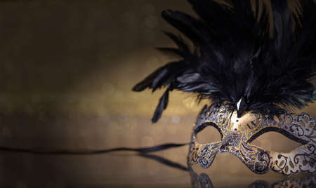 Carnival time. Venetian mask with feathers on dark golden background, reflections, copy space Imagens