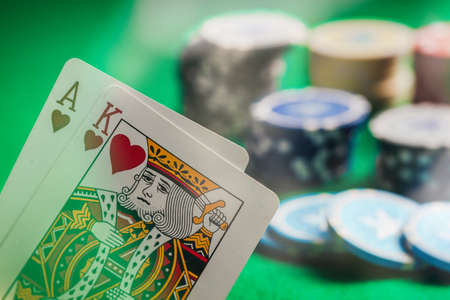 Casino, gambling concept. Ace and king hearts and poker chips on green felt abstract background
