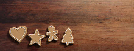 Christmas preparation, gingerbread cookies. Top view of christmas gingerbread cookies, isolated, against wooden background, copy space, banner. 3d illustration