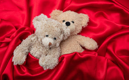 Love, valentines day concept, tight hug. Two teddy bears embracing as a couple in bed, red satin background