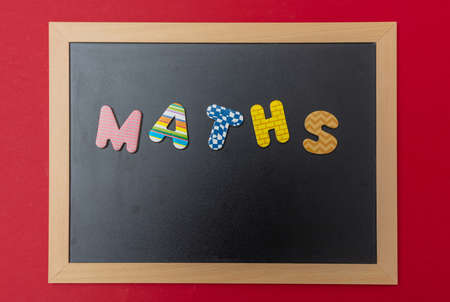 School maths concept. Black chalkboard with wooden frame, word, text maths in colorful letters, red wall background Stockfoto