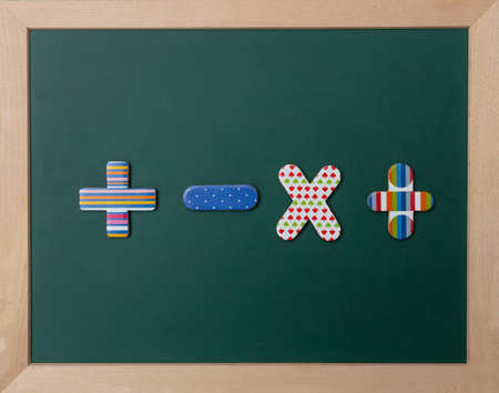 Matemáticas, concepto de escuela. Pizarra verde con marco de madera, coloridos carteles de operación Foto de archivo
