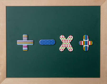 Mathématiques, concept d'école. Tableau vert avec cadre en bois, panneaux d'opération colorés Banque d'images