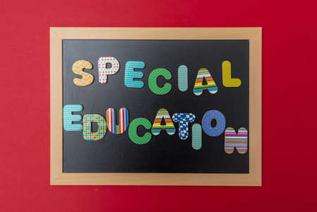 Special education concept. Black chalkboard with wooden frame, text special education in colorful letters, red wall background