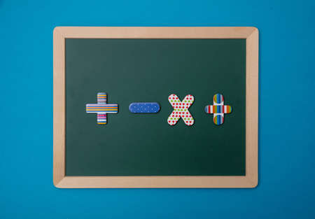 Math, school concept. Green chalkboard with wooden frame, colorful operation signs, blue background