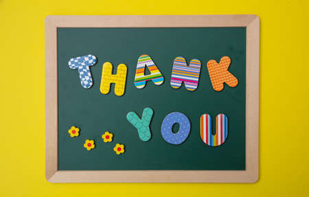 Thank you, Colorful letters shaping the word thank you on green board with wooden frame, yellow wall background Фото со стока