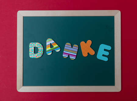 Danke, thank you, Colorful letters shaping the word Danke, thank you in german, on green board with wooden frame, red wall background