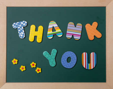 Thank you, Colorful letters shaping the word thank you on green board with wooden frame