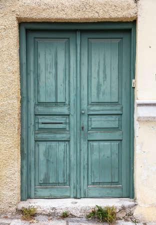 Puerta verde de madera desgastada y descolorida, entrada de la casa cerrada. Fachada de edificio tradicional, casco antiguo de Plaka, Atenas Grecia