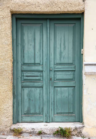 Wooden worn and faded green door, closed house entrance. Traditional building facade, old town of Plaka, Athens Greece