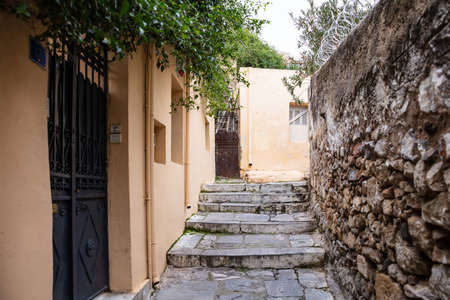 Plaka, Athens Greece. Old town narrow pedestrian streets and stairs, houses facades and stone walls. Low angle, perspective view
