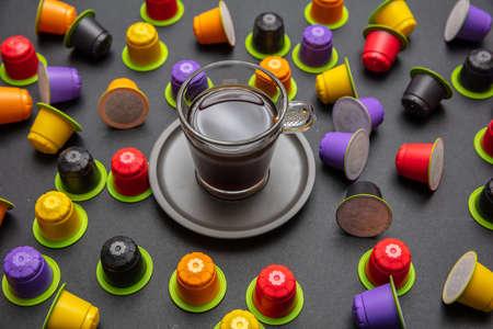 Taza de café y cápsulas, respetuosas con el medio ambiente, compostables sobre fondo de color negro
