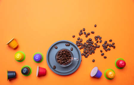 Coffee cup, beans and capsules, pods, on bright orange color background, copy space, top view Stockfoto