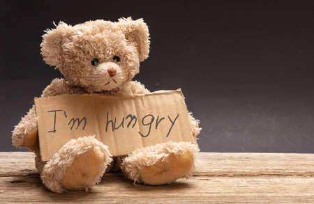 Homeless hungry child concept. Teddy bear sad, holding a cardboard sign, text I am hungry, black background Stock Photo