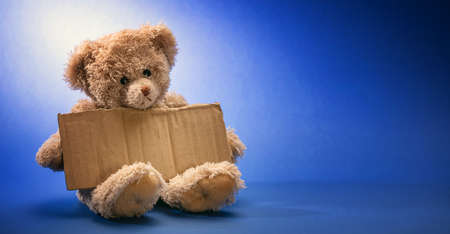 Pauvre enfant sans-abri mendiant. Ours en peluche triste, tenant une pancarte en carton vierge, assis sur fond bleu, espace pour copie