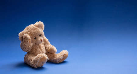 Blue Monday, depression concept. Teddy bear sad, holding his head, sitting in blue empty room background, copy space