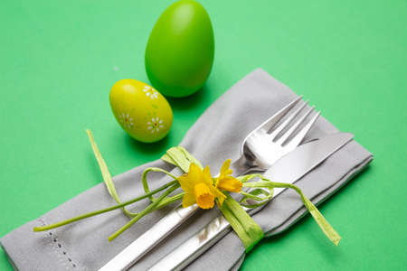Easter table, place setting. Easter eggs, painted, cutlery and grey napkin, green color background, close up view