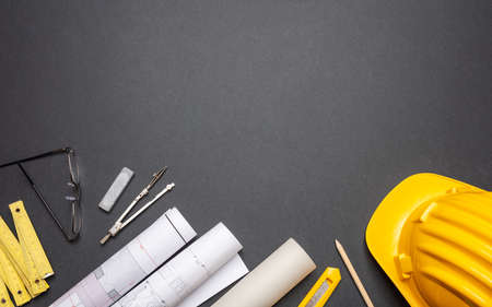 Architect engineer workplace, construction site desk. Project blueprints, yellow hard hat and engineering tools on black, copy space, top view