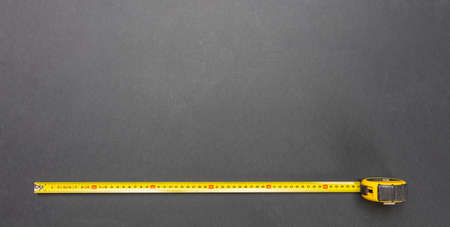 Measuring. Yellow measure tape isolated on black color background, top view, copy space 스톡 콘텐츠