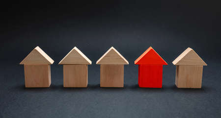 House choice, selection, property and real estate concept. Red house model among wooden houses, black color background Stock Photo