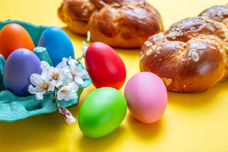 Easter eggs and tsoureki braid, greek easter sweet bread, on yellow color background Stock Photo