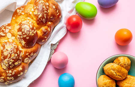 Easter eggs and tsoureki braid, greek easter sweet bread, on pink color background, top view Фото со стока