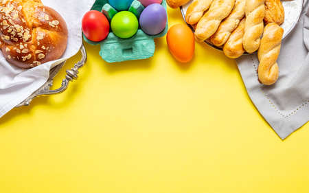 Easter eggs and tsoureki braid, greek easter sweet bread, on yellow color background, top view, copy space